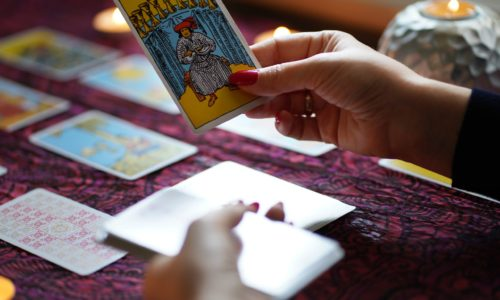 Tarot reader picking tarot cards.Tarot cards on table near burning candles.Candlelight in dark.Tarot reader or Fortune teller reading